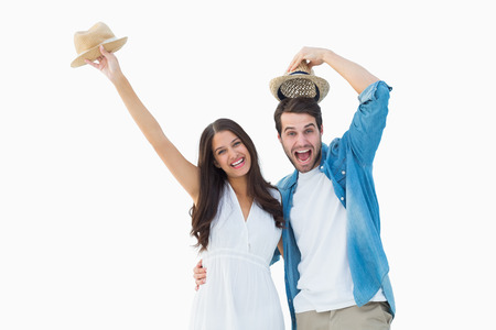 Happy hipster couple smiling at camera and cheering on white background photo