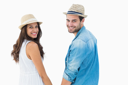 Happy hipster couple holding hands and smiling at camera on white background photo