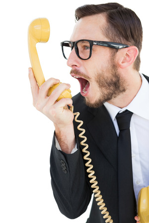 phoning: Geeky businessman shouting at telephone on white background