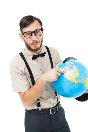 Geeky hipster pointing to globe on white background photo