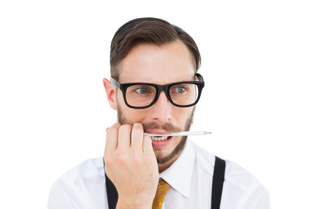Geeky hipster biting on pencil on white background photo