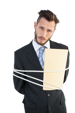 Serious businessman tied up at work on white background photo