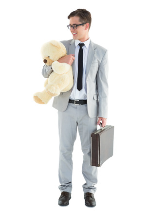 Handsome businessman holding briefcase and teddy on white background photo