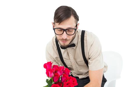 heartbroken: Geeky heartbroken hipster holding roses on white background Stock Photo