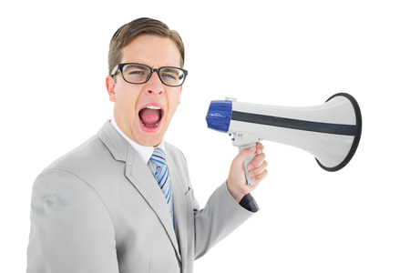 Geeky businessman shouting through megaphone on white background photo