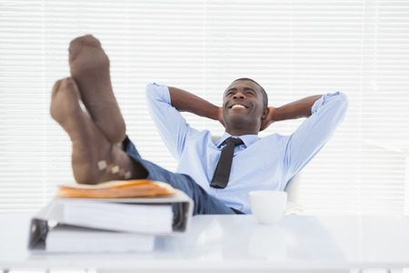 Relaxed businessman sitting in his chair with feet up in his office photo