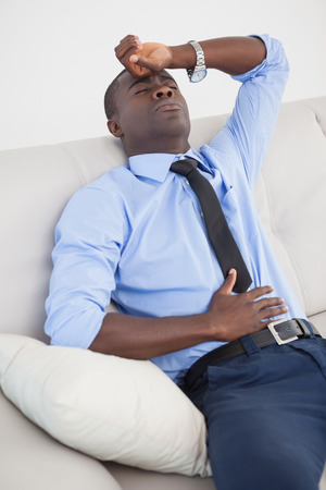 wincing: Tired businessman getting a headache at home in the living room