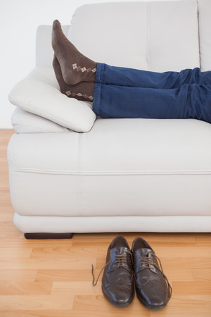 brogues: Tired businessman lying on sofa with shoes off at home in the living room