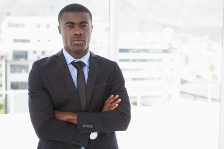 hombres negros: Apuesto hombre de negocios con el ceño fruncido a la cámara en su oficina Foto de archivo
