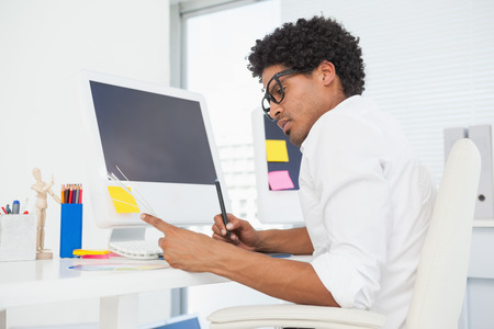 Hipster designer working at his desk in his office photo