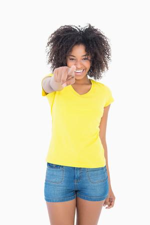 mujeres africanas: Muchacha bonita en pantalones calientes de la camiseta amarilla y denim apuntando a la cámara sobre fondo blanco