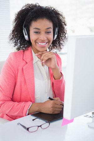 Casual graphic designer working at her desk smiling at camera in her office photo