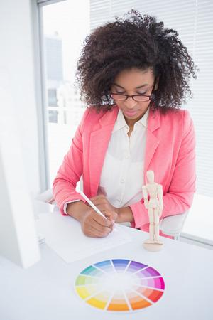 mannequin africain: Graphiste Casual travaillant à son bureau croquis dans son bureau