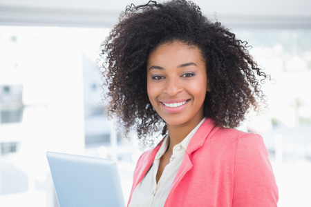 Casual businesswoman smiling at camera holding tablet pc in her office photo