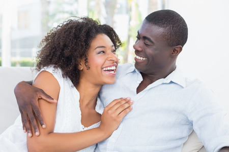 pareja abrazada: Atractiva pareja de mimos en el sof� en casa en la sala de estar