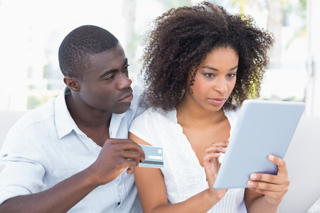 Attractive couple using tablet together on sofa to shop online at home in the living room photo
