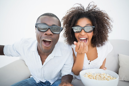 Couple sitting on couch together watching 3d movie at home in the living room photo