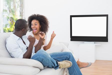 vzrušený: Pár sedí na gauči, sledování televize doma v obývacím pokoji