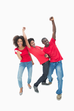 Football fans in red cheering together on white background photo