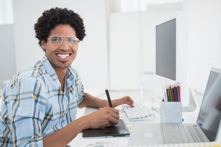 Young designer working at his desk with digitizer in his office photo