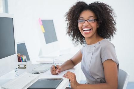 Junge hübsche Designer lächelt Kamera auf ihrem Schreibtisch in ihrem Büro