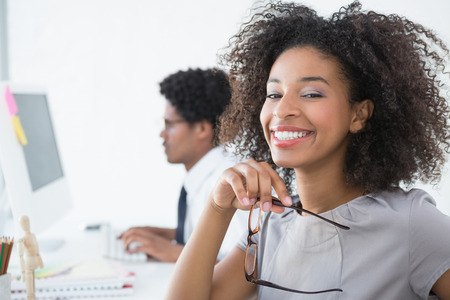 african american woman business: Young editor smiling at camera at her desk in creative office