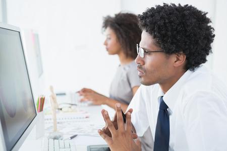 mannequin africain: Jeune designer regardant l'ordinateur à son bureau dans le bureau de création