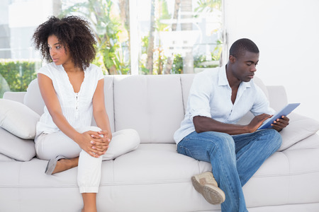 Attractive couple not talking on the couch at home in the living room photo