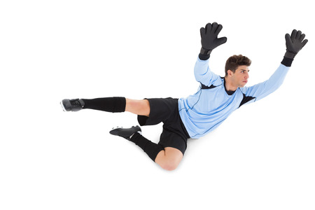 making a save: Goalkeeper in blue making a save on white background