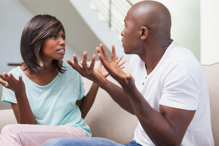 Angry couple having a dispute on sofa at home in the living room photo