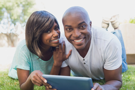 Happy couple lying in garden using tablet pc together on a sunny day photo