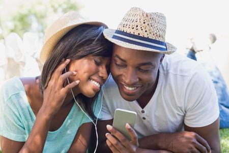 hombres negros: Feliz pareja acostada en el jardín juntos escuchando música en un día soleado
