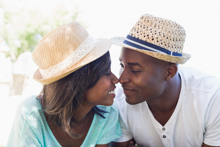Happy couple lying in garden together touching noses on a sunny day Stock Photo