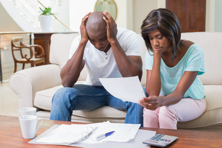 Stressed couple calculating bills on the couch at home in the living room photo