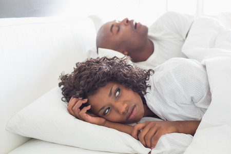 Annoyed woman lying in bed with snoring boyfriend at home in the bedroom photo