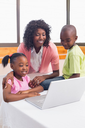 Cute siblings using laptop together with mother at home in the kitchen photo