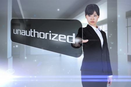 unauthorized: Businesswoman pointing to word unauthorized against screen in room with sparks Stock Photo