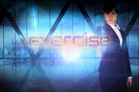 Businesswoman presenting the word exercise against room with large window looking on city photo