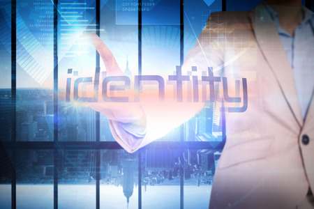 Businesswoman presenting the word identity against room with large window looking on city photo