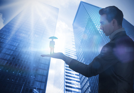 Composite image of businessman holding business man holding umbrella against low angle view of skyscrapers photo