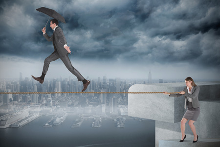 Young businesswoman pulling a tightrope for businessman against coastline and city photo