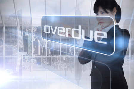 overdue: Businesswoman looking at the word overdue against room with large window looking on city