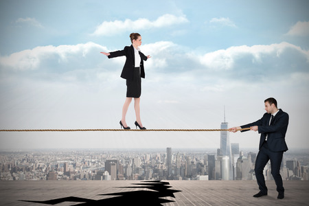 Young business man pulling a tightrope for businesswoman against cracked balcony overlooking city photo