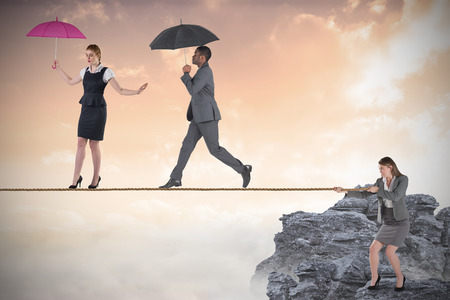 Young business woman pulling a tightrope for business people against white background with vignette photo