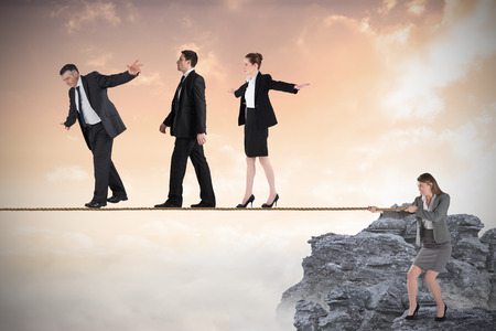 tight focus: Young businesswoman pulling a tightrope for business people against rocky landscape