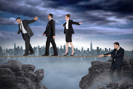 tight focus: Young businessman pulling a tightrope for business people against large city on the horizon Stock Photo