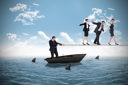 Young businessman pulling a tightrope for business people against sharks circling small boat in the ocean photo