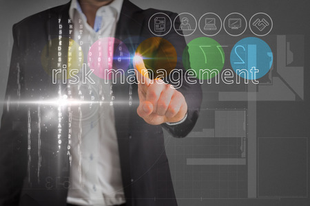 Businessman touching the words risk management on interface against grey vignette photo