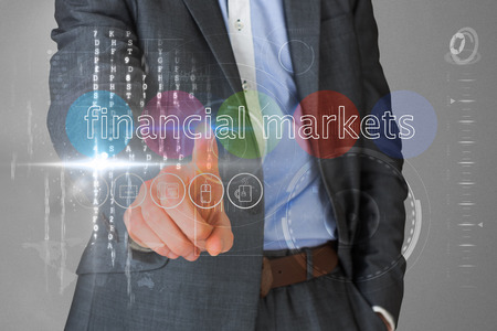Businessman touching the words financial markets on interface against grey vignette photo