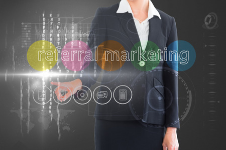Businesswoman touching the words referral marketing on interface against grey vignette photo